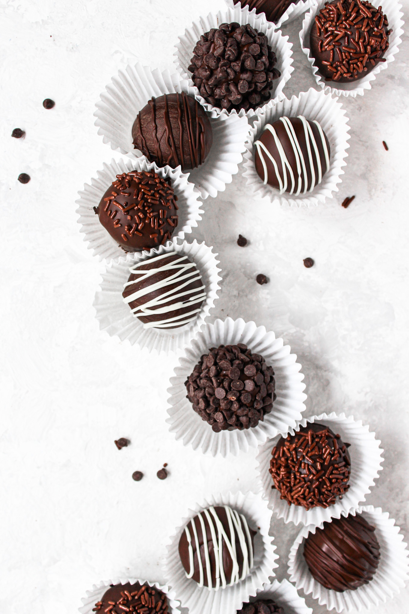 Flatlay of chocolate truffles in a curved line with mini chocolate chips around it
