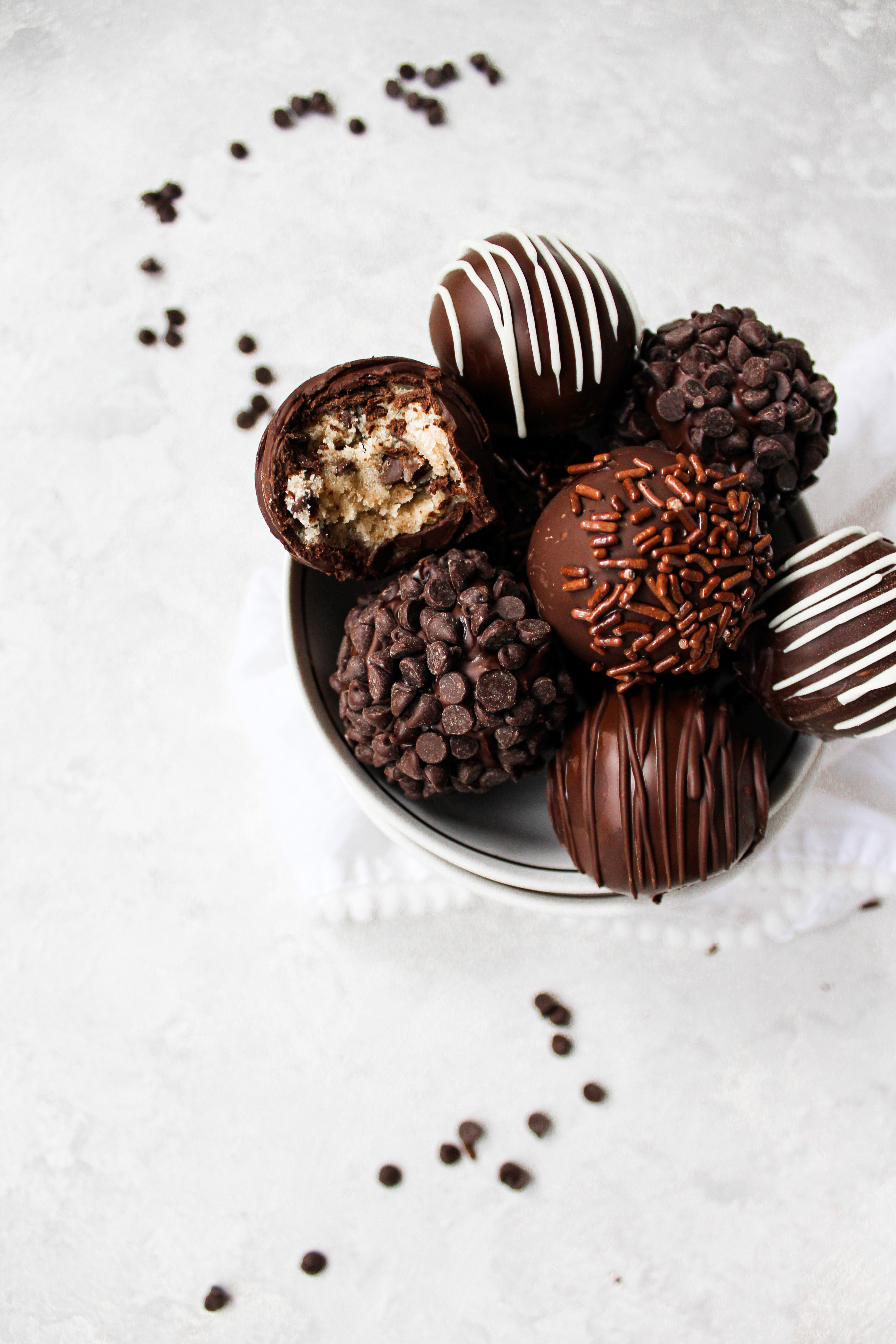 cookie dough truffles in a bowl with one bite out one of the truffles