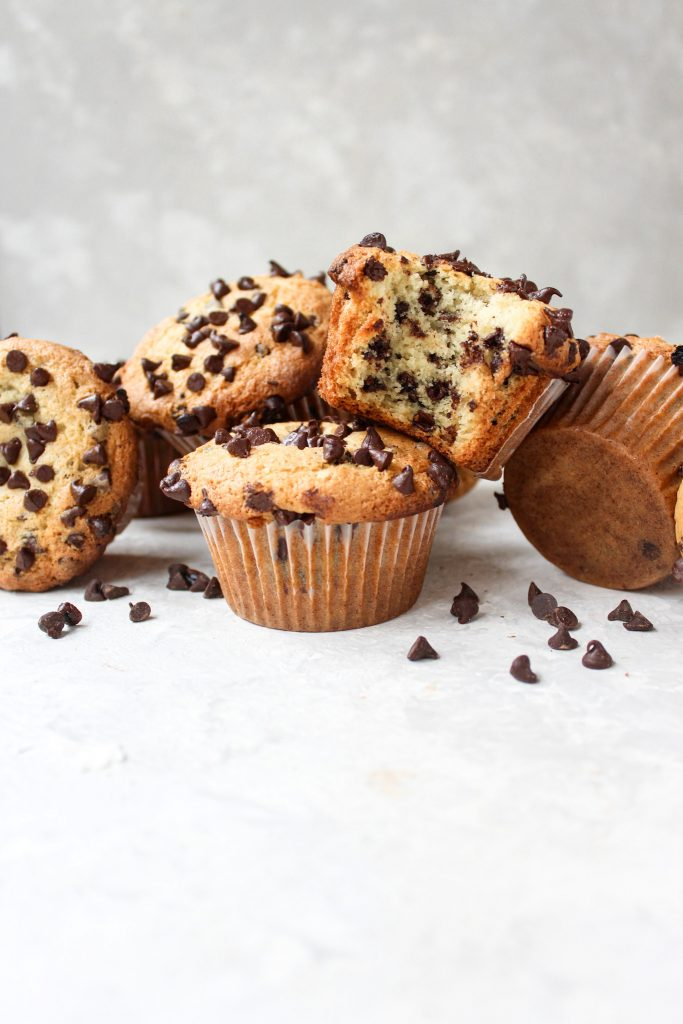straight-on shot of a line of messy muffins with a large bite taken out of the center muffin