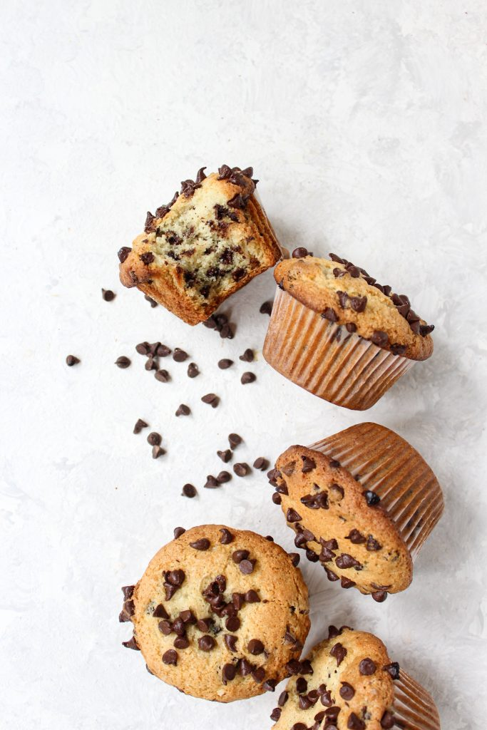 overhead shot of a curved line of muffins surrounded by mini chocolate chips