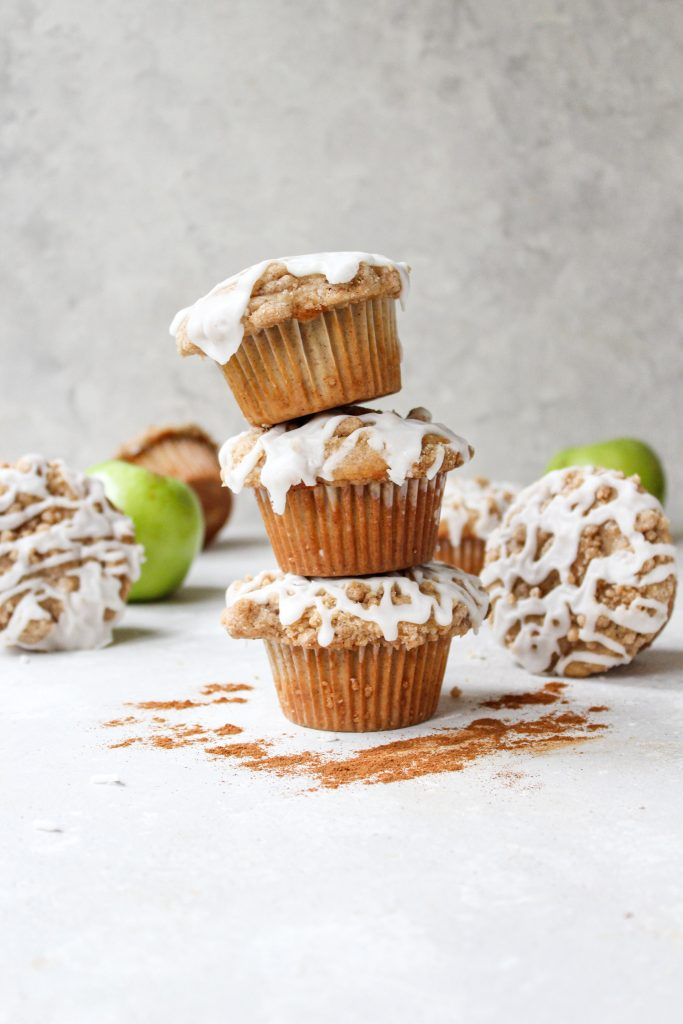 tall stack of 3 apple crumb muffins surrounded by cinnamon