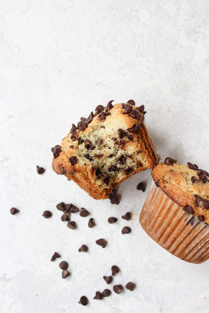 2 bakery muffins on their sides, one with a bite taken out of it