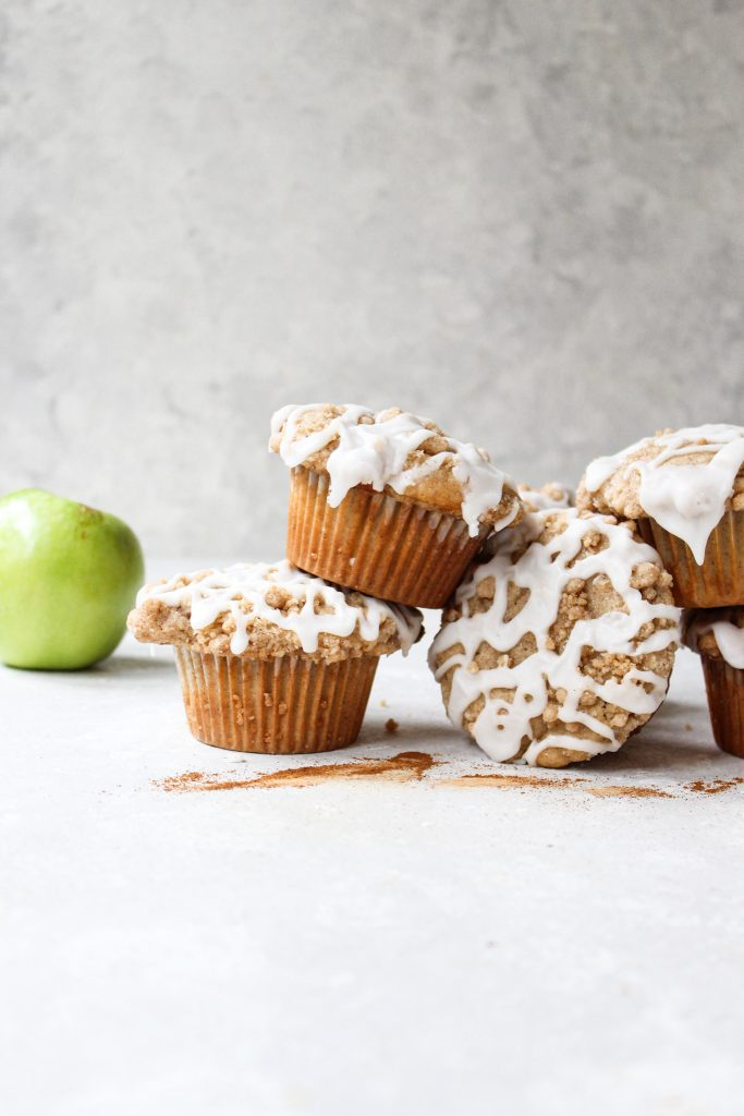 stack of muffins with glaze, cinnamon, and a green apple in the background