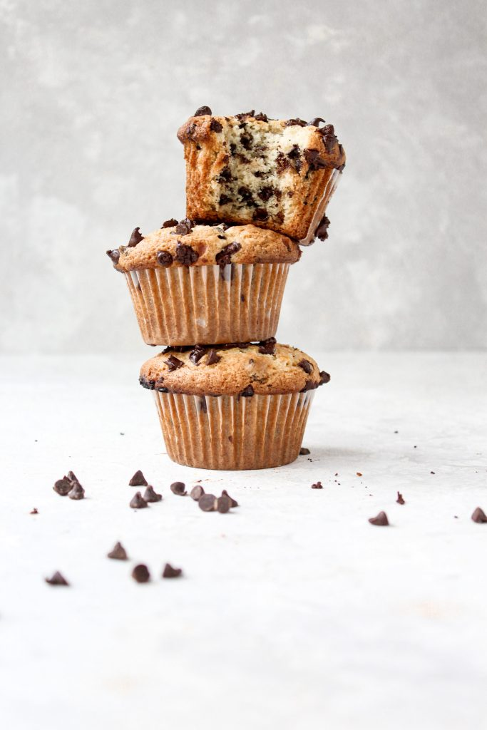 3 stacked muffins surrounded by mini chocolate chips with a bite taken out of the top muffin