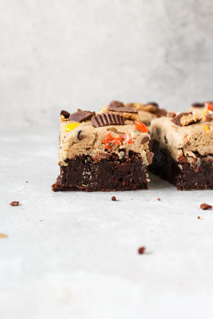 cookie dough brownies standing next to one another surrounded by crumbs
