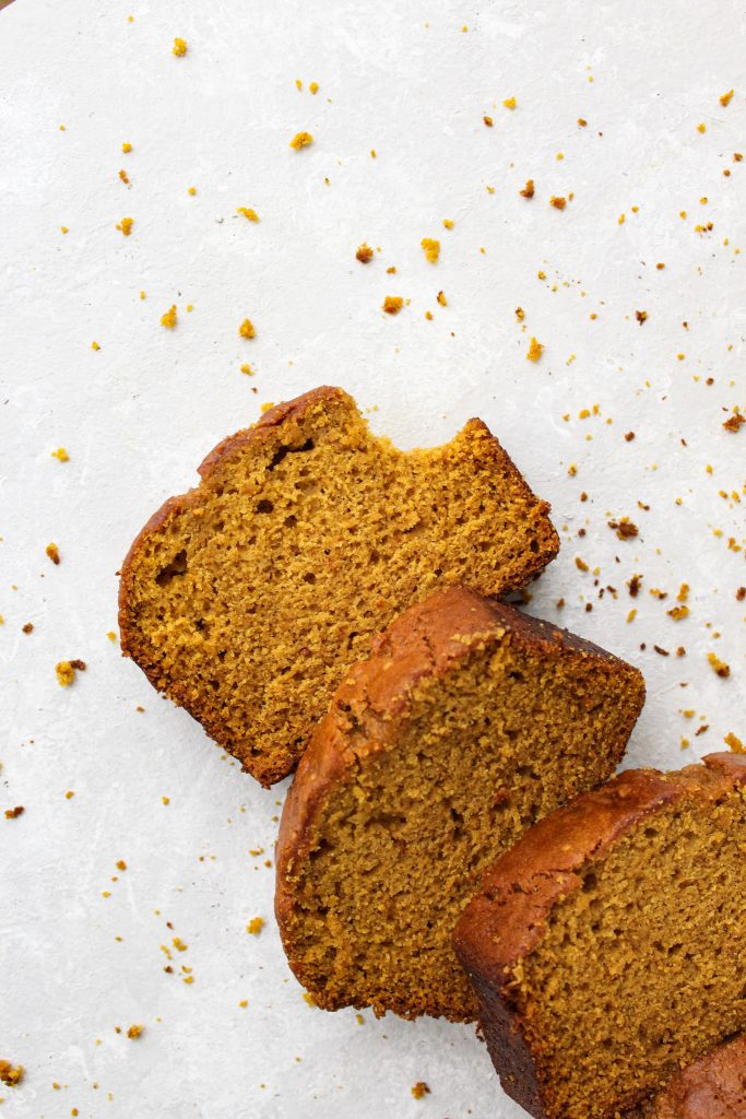 Diagonal line of pumpkin loaf slices surrounded by crumbs