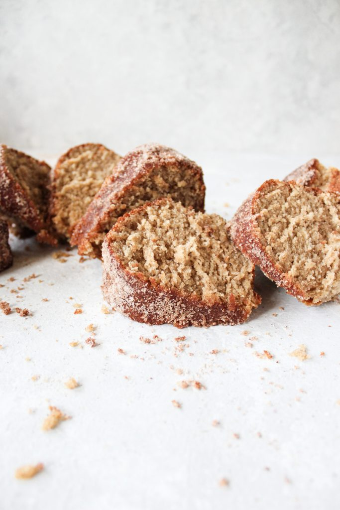 staggered apple cider bundt pieces surrounded by cinnamon sugar