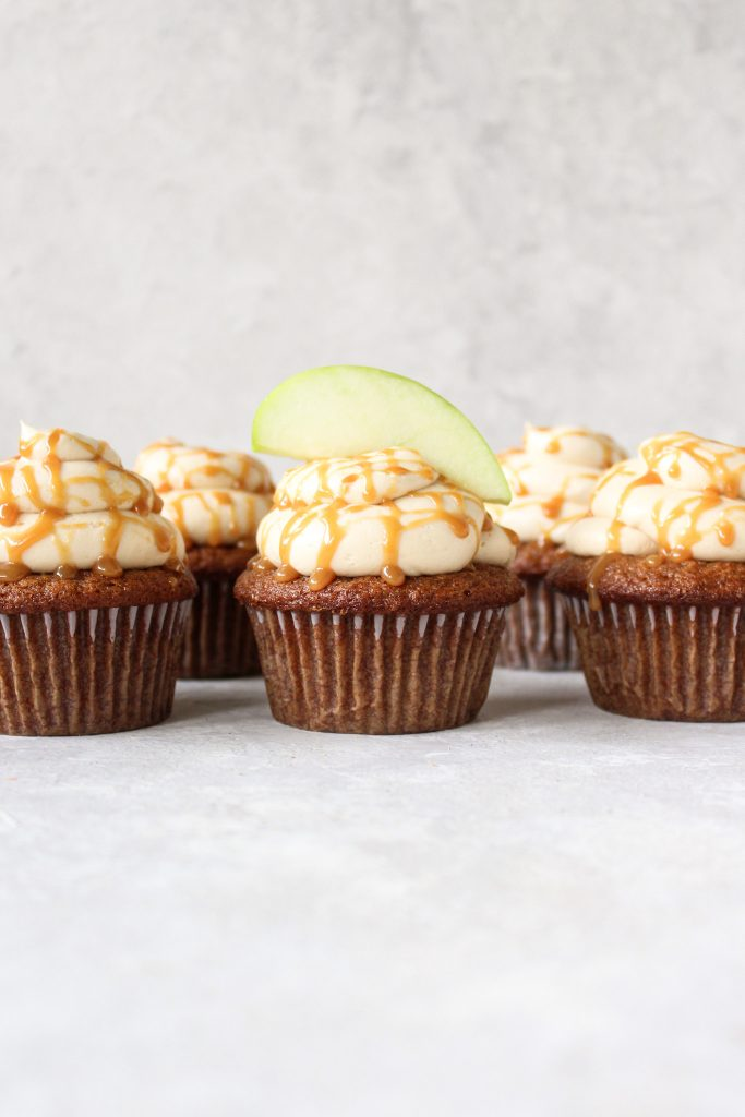 rows of apple cider cupcakes with a green apple slice sitting on top of the middle cupcake
