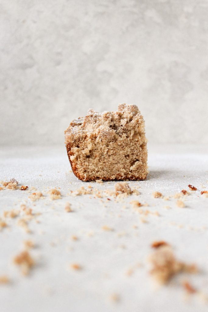 single square of apple cider cake surrounded by crumb topping
