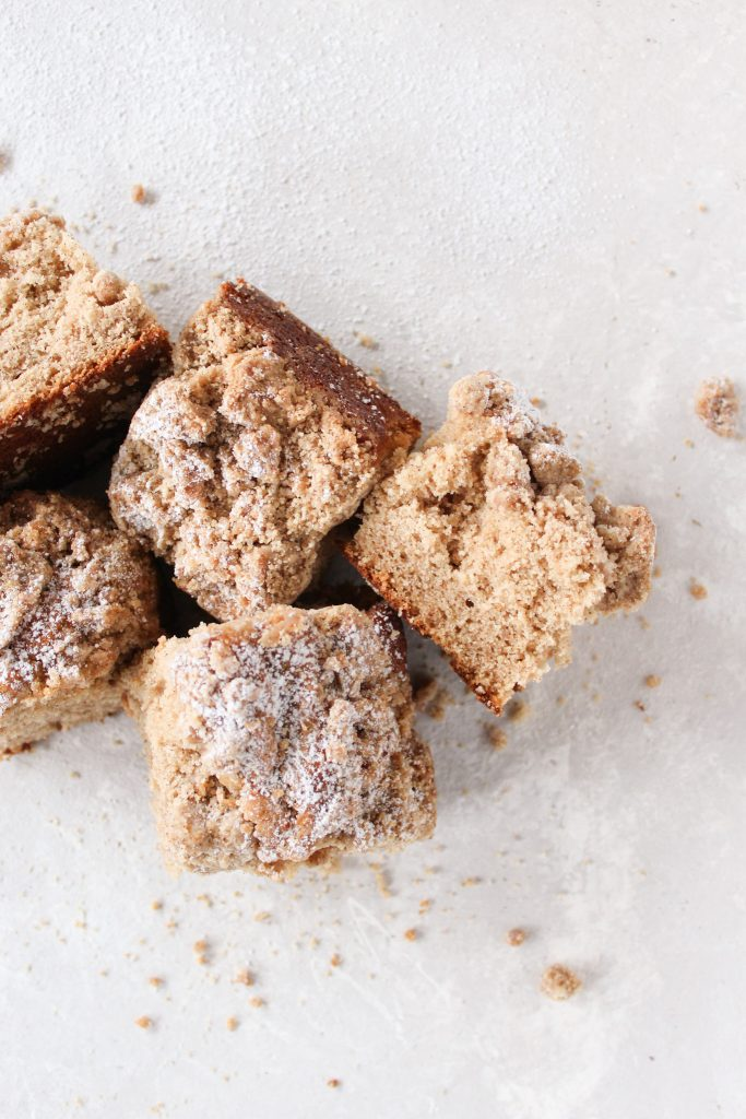 horizontal line of crumb cake pieces surrounded by crumbs and powdered sugar